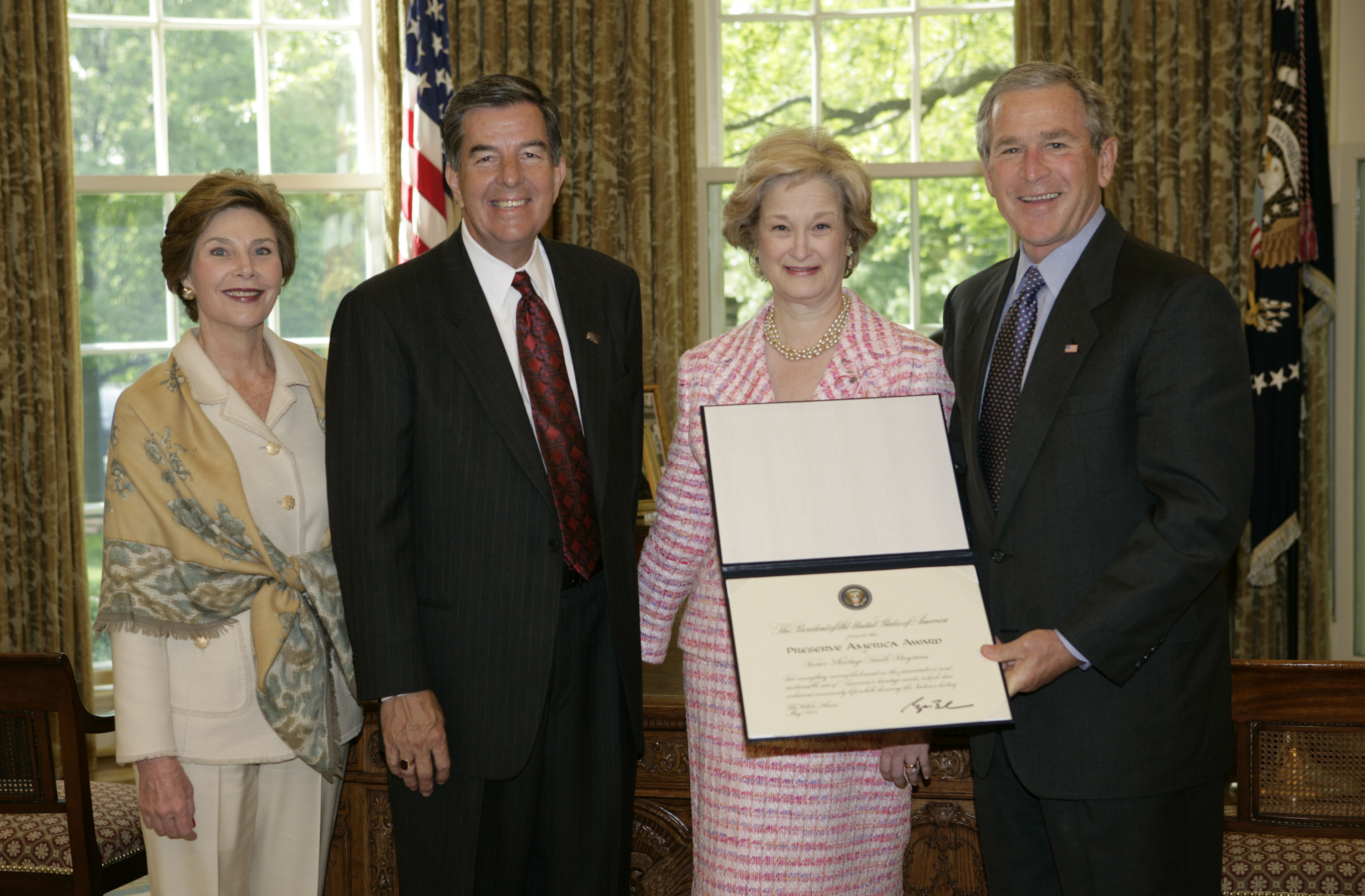 President George W. Bush and Laura Bush present the 2005 Preserve America Presidential Award to members of the Texas Historical Commission in the Oval Office Monday, May 2, 2005. They are Larry Oaks, Executive Director, of Leander, Texas, and Diane Bumpas, Commissioner, of Dallas. (White House photo by Eric Draper)