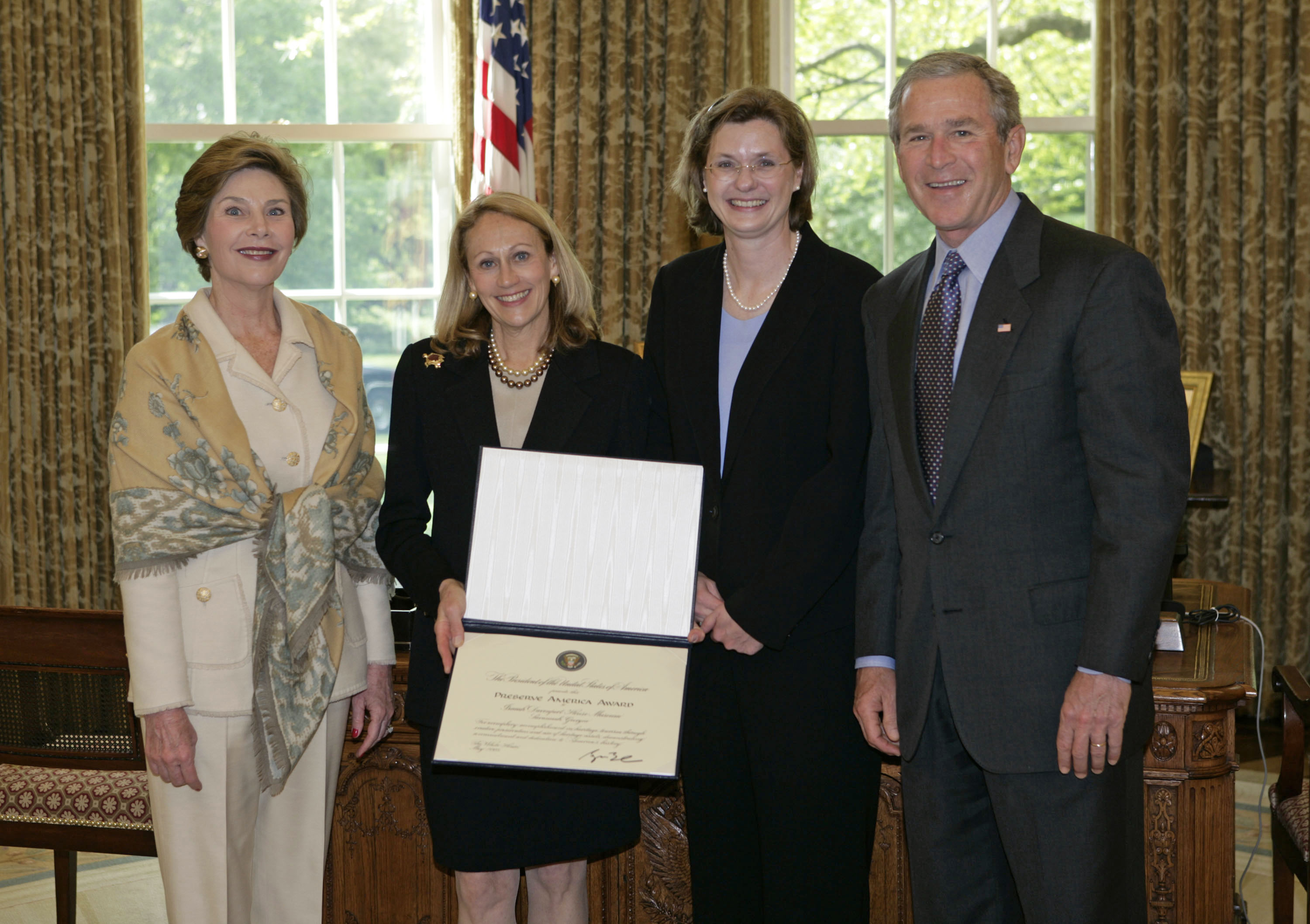 President George W. Bush and Laura Bush present the 2005 Preserve America Presidential Award to Zelda Tenenbaum, President, Board of Trustees, Historic Savannah Foundation, left, and Jamie Credle, Director, Isaiah Davenport House Museum, both of Savannah, Georgia, in the Oval Office Monday, May 2, 2005. (White House photo by Eric Draper)