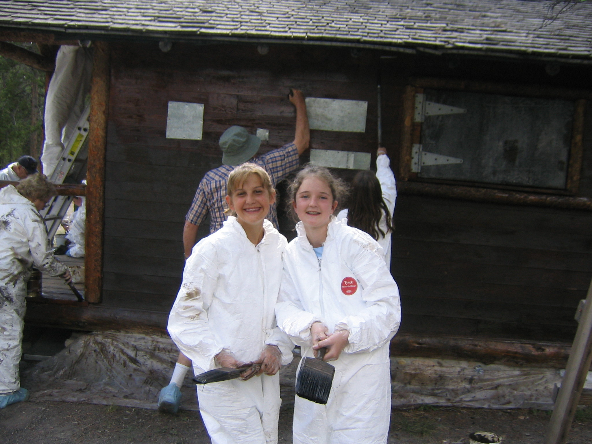 Two young guest volunteers at Yellowstone participate in staining a historic cabin.