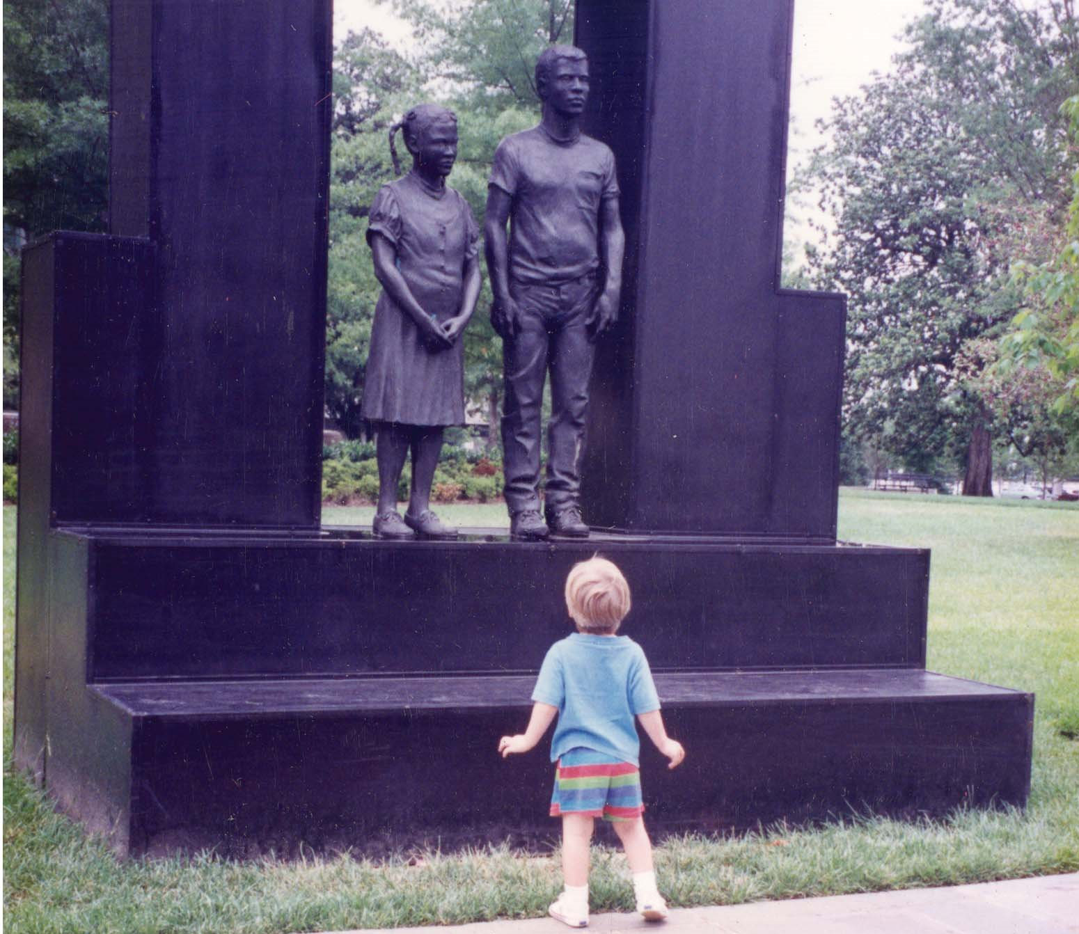 A child looks up at a sculpture commemorating the Children's March in Kelly Ingram Park at the Civil Rights Museum