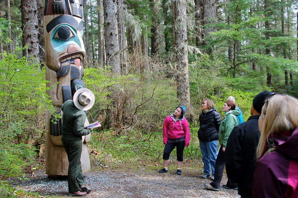 A Park Ranger leads a totem pole tour in Sitka National Historic Park.