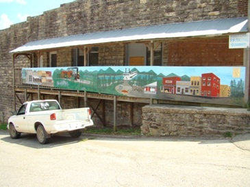 A colorful mural depicting the town on a stone building in Calico Rock, Arkansas.