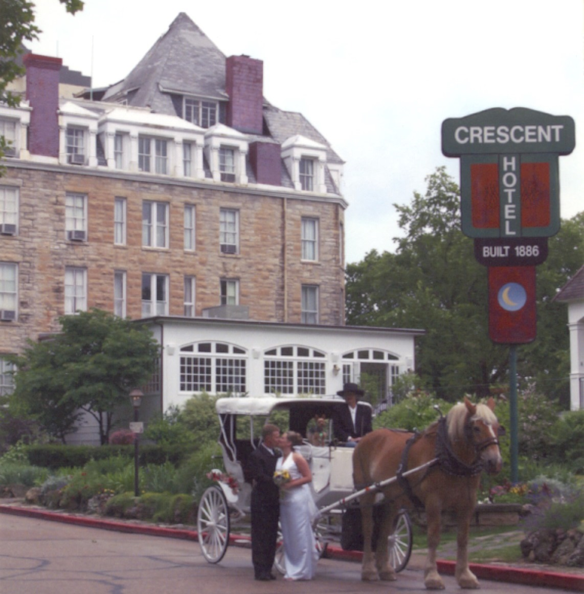 A newly married couple poses in front of the Crescent Hotel (1886) in historic Eureka Springs, Arkansas