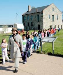 Young visitors to historic Fort Smith explore the historic site with a costumed guide