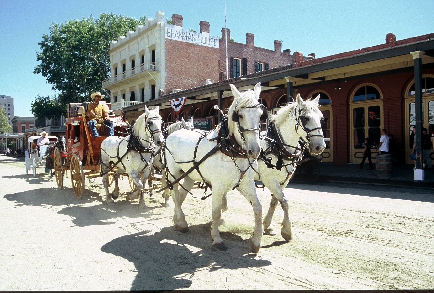 Horses pull a stagecoach past historic buildings during Gold Rush Days in Sacramento, California