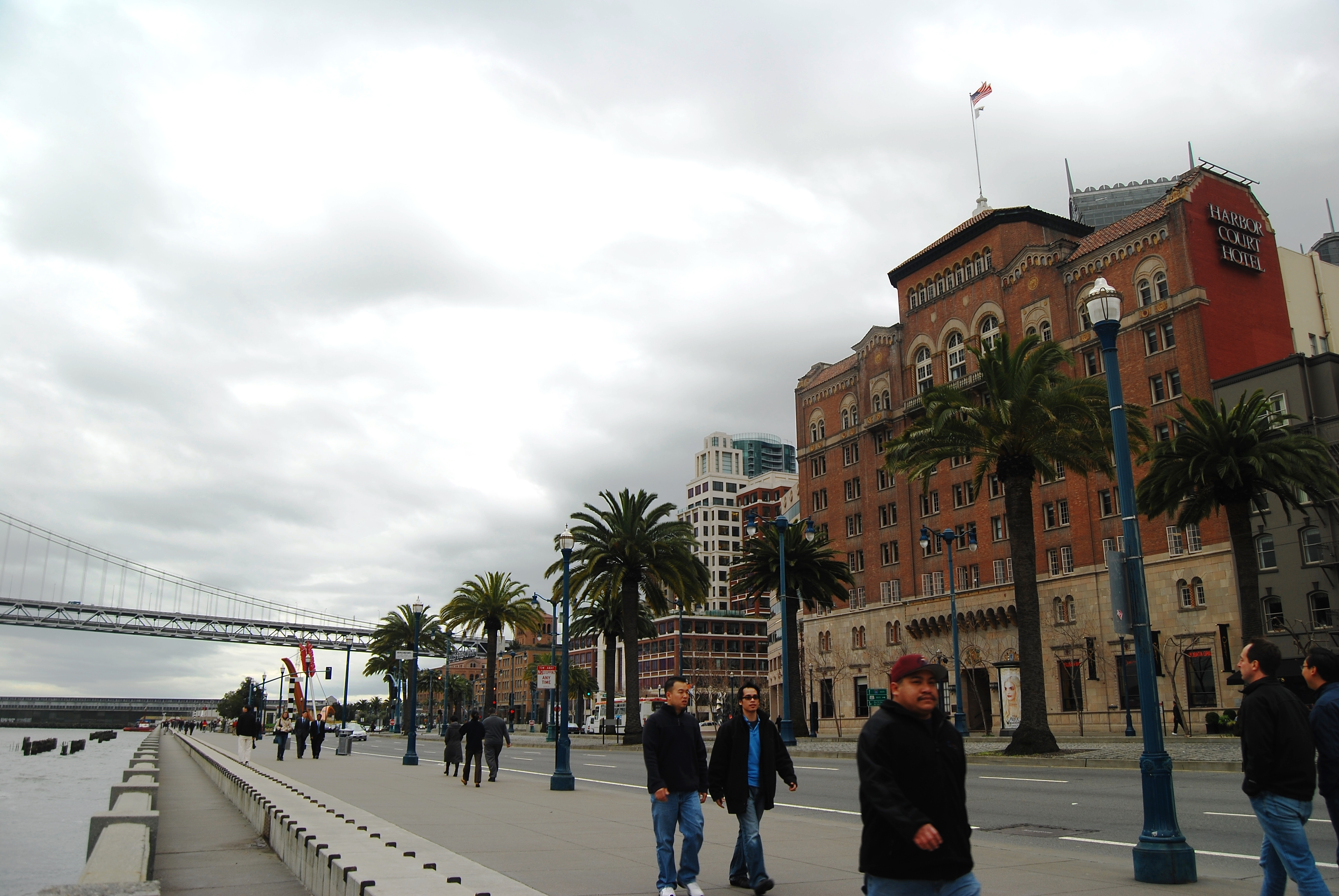 People walk along the Embarcadero in San Francisco on a cloudy day