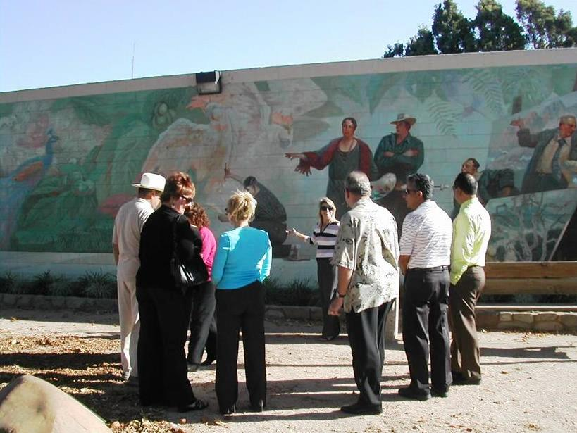 A docent led tour group explores murals depict significant developments in Santa Paula's history