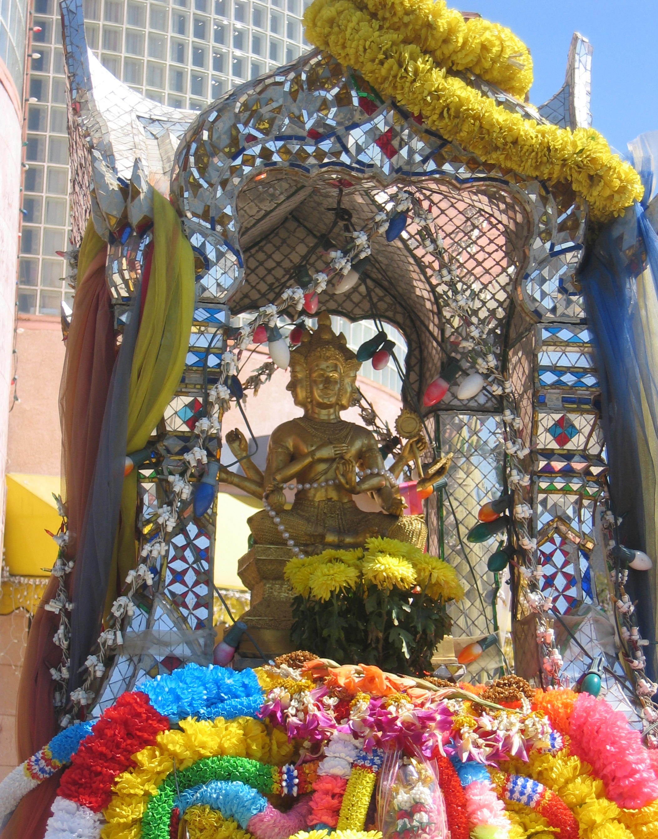 A traditional Thai Spirit House receives gifts, garlands, and prayers from the Thai community. This spirit house, a mosaic of glass and tile, is one of two located within Thai Town in Los Angeles.