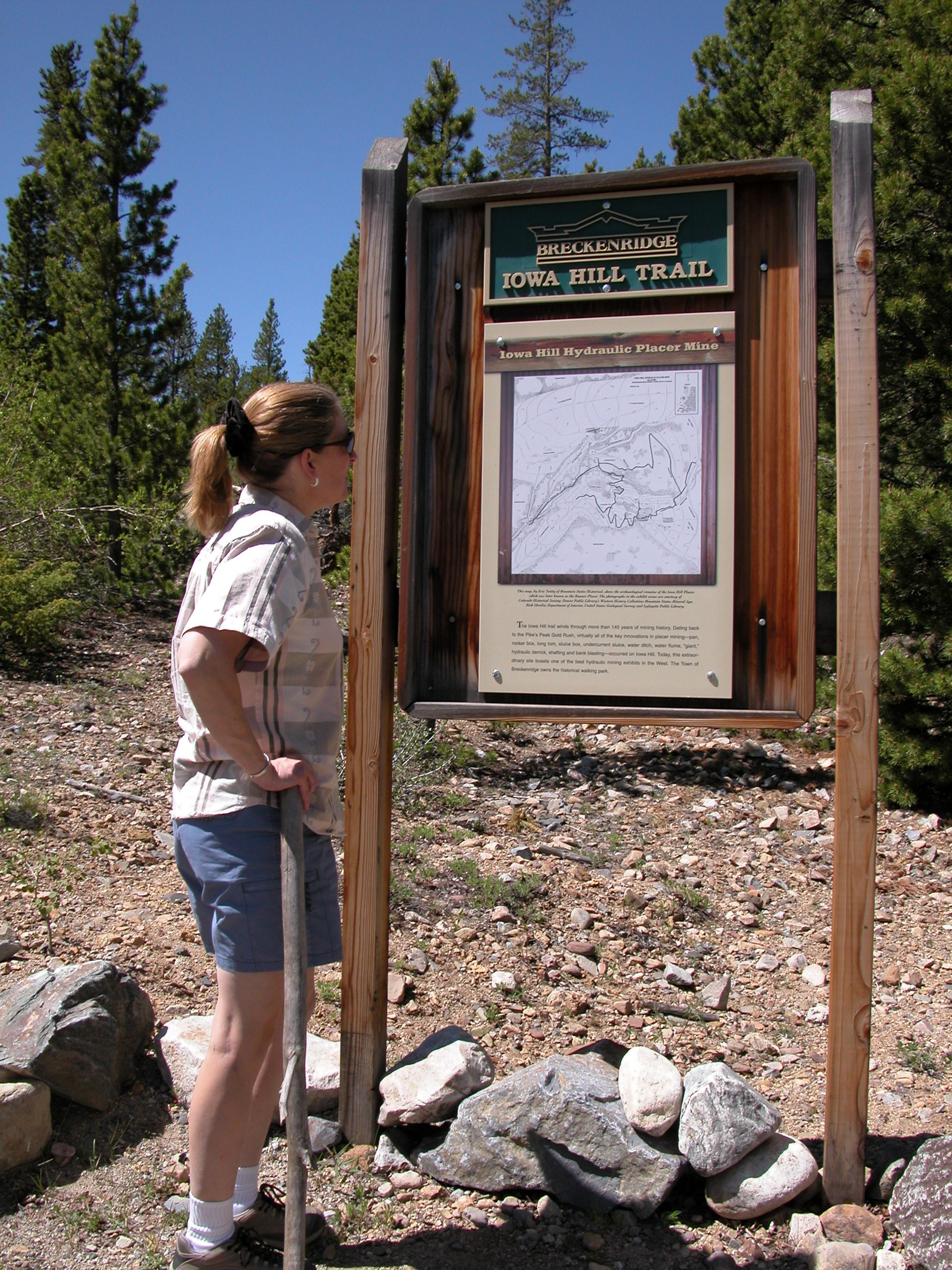 A woman studies a map at the trailhead leading to the Iowa Hill Hydraulic Placer Mine. Historic mining sites are central to the heritage of Breckenridge, Colorado.