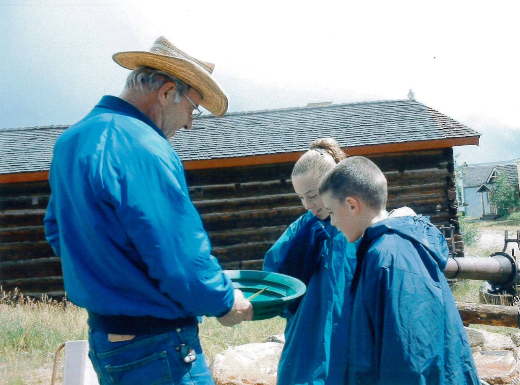 Local man in period dress helps kids pan for gold on Community Day at the South Park City Museum in Park County, Colorado.