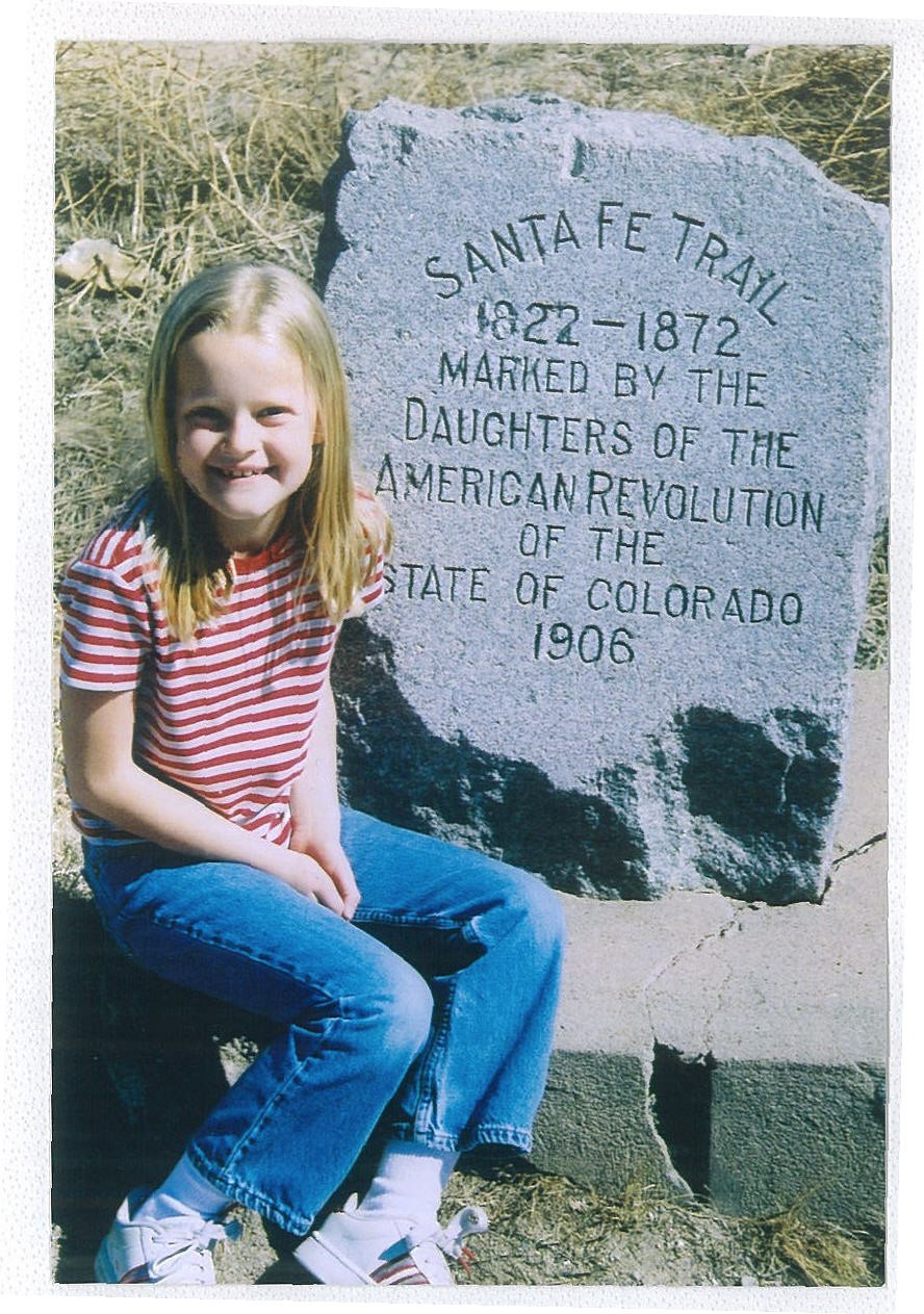 A young girl poses by a Santa Fe Trail marker erected in 1906