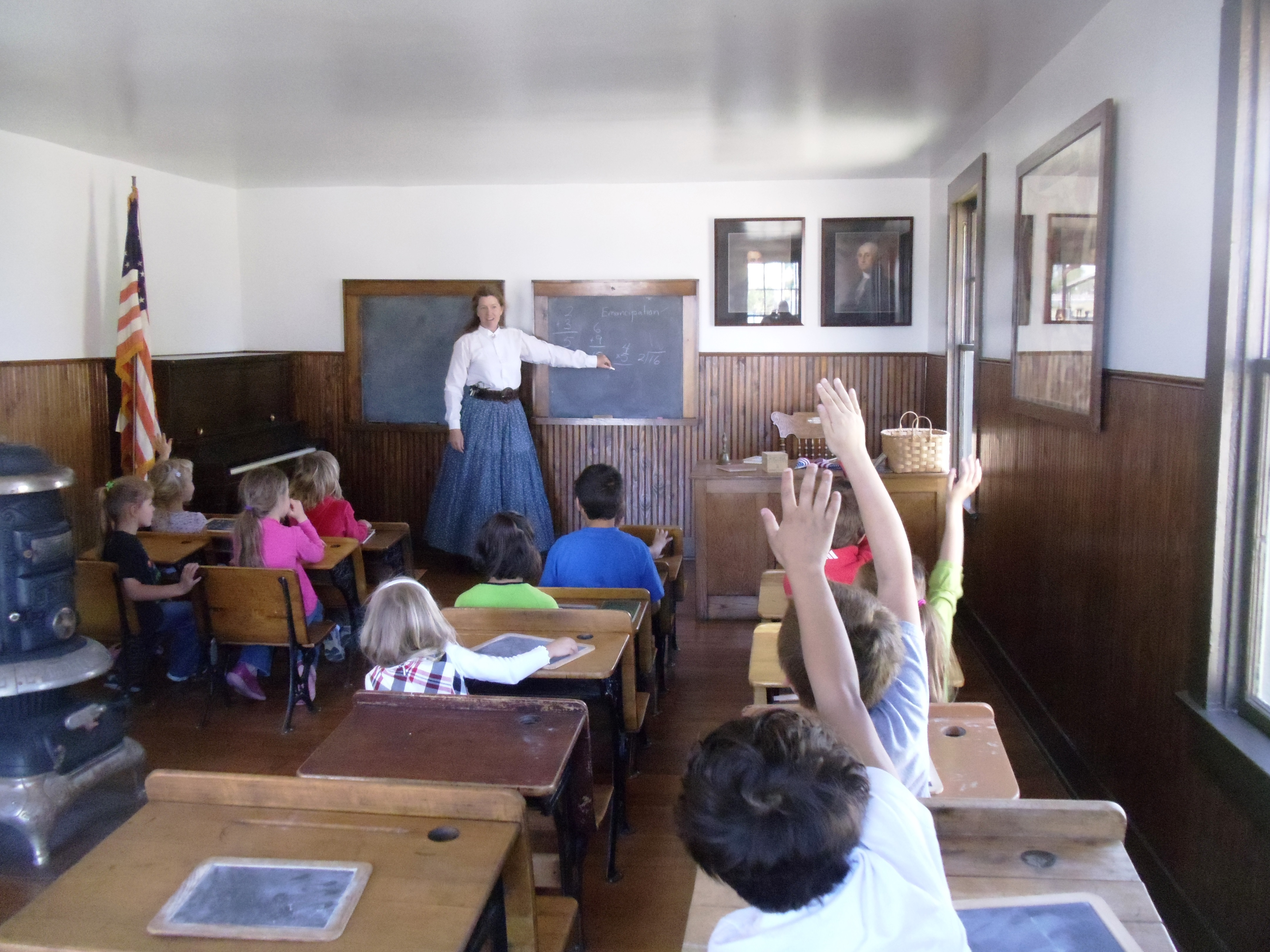 The historic Whitehall Schoolhouse offers students the opportunity to experience learning in a historic classroom with a teacher in period costume.