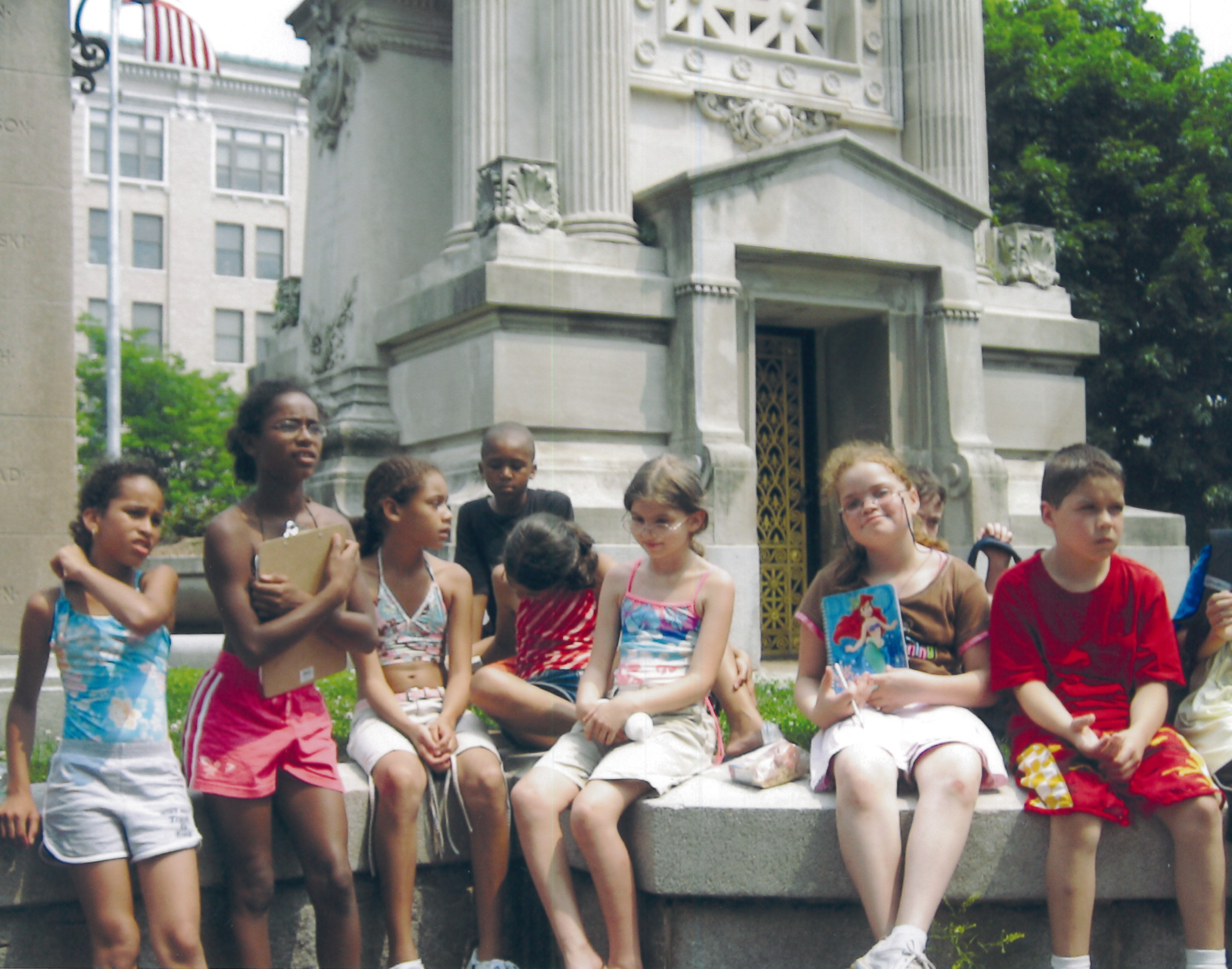 Children sit on a monument in New Britain's historic Central Park