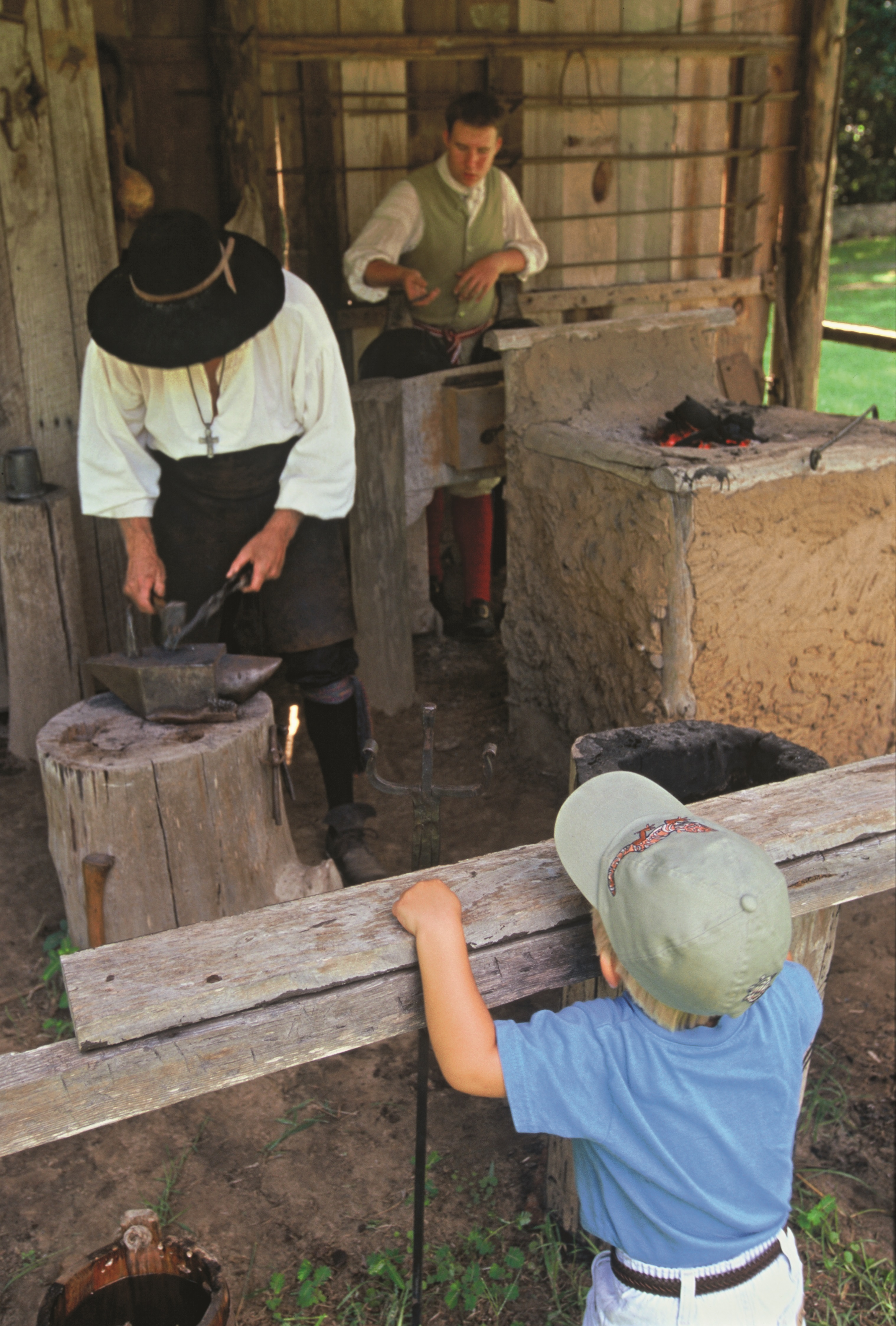A young boy watches blacksmiths working at a forge at Mission San Luis in Leon County, Florida. The Mission was awarded a Preserve America Presidential Award for heritage tourism in 2006.