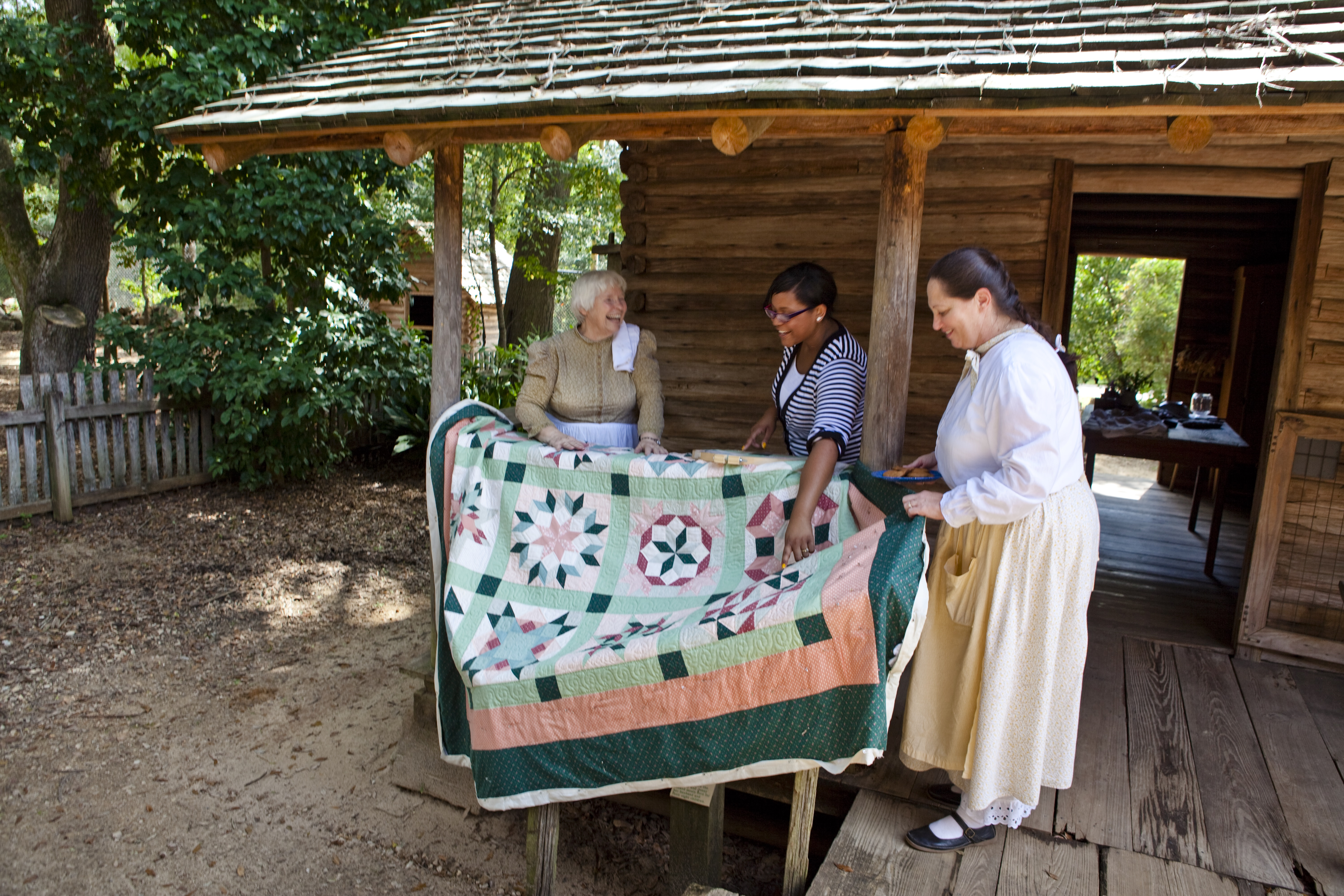 Living history interpreters show a visitor a completed quilt at the Tallahassee Museum of Natural History and Science.