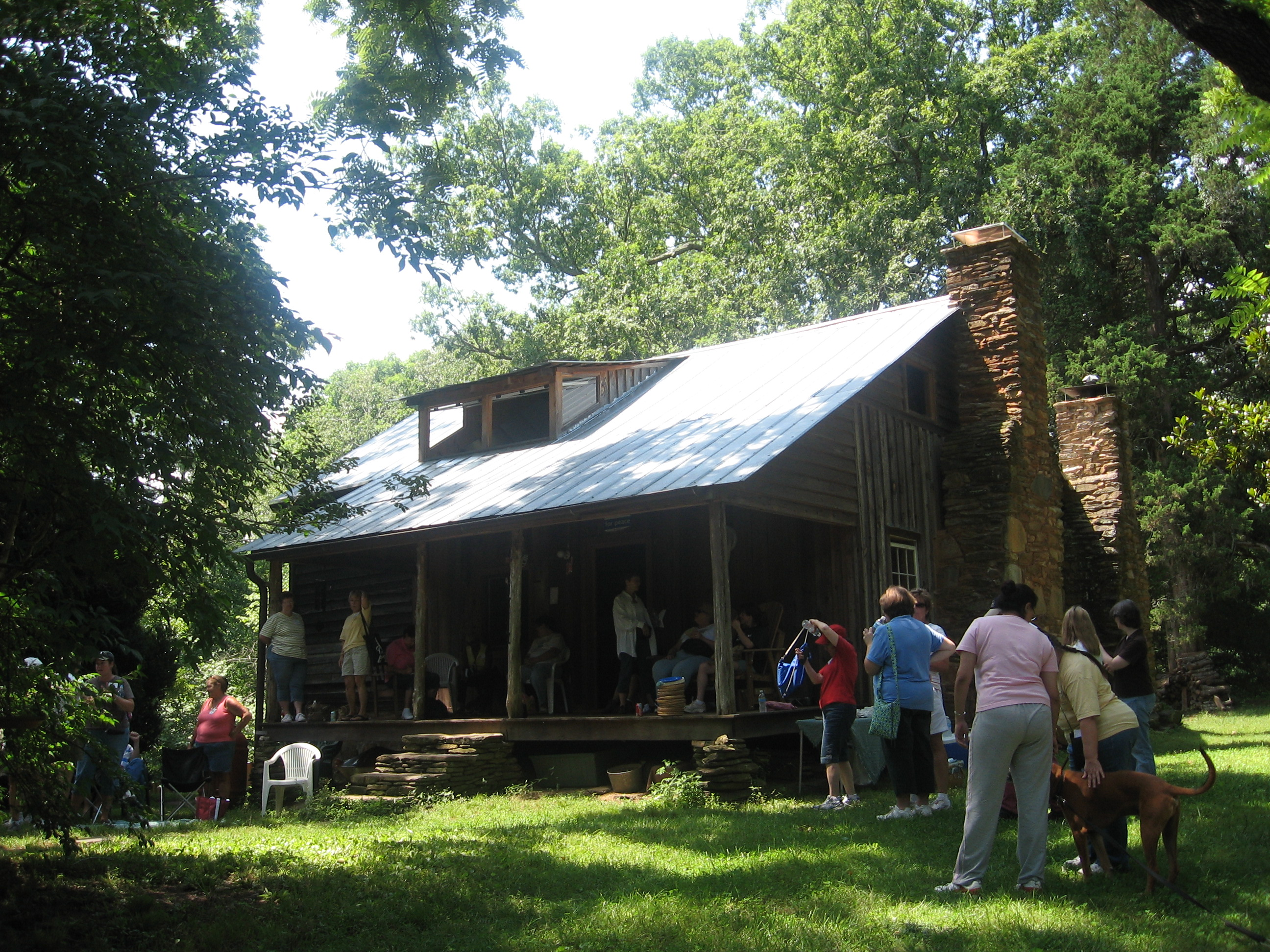 Visitors at the circa 1843 Power Cabin, one of the rare examples of a single-pen (one room) log house remaining in Cobb County. Although a framed addition was added later, the original hand-hewn, squared-and-notched log construction is still visible.