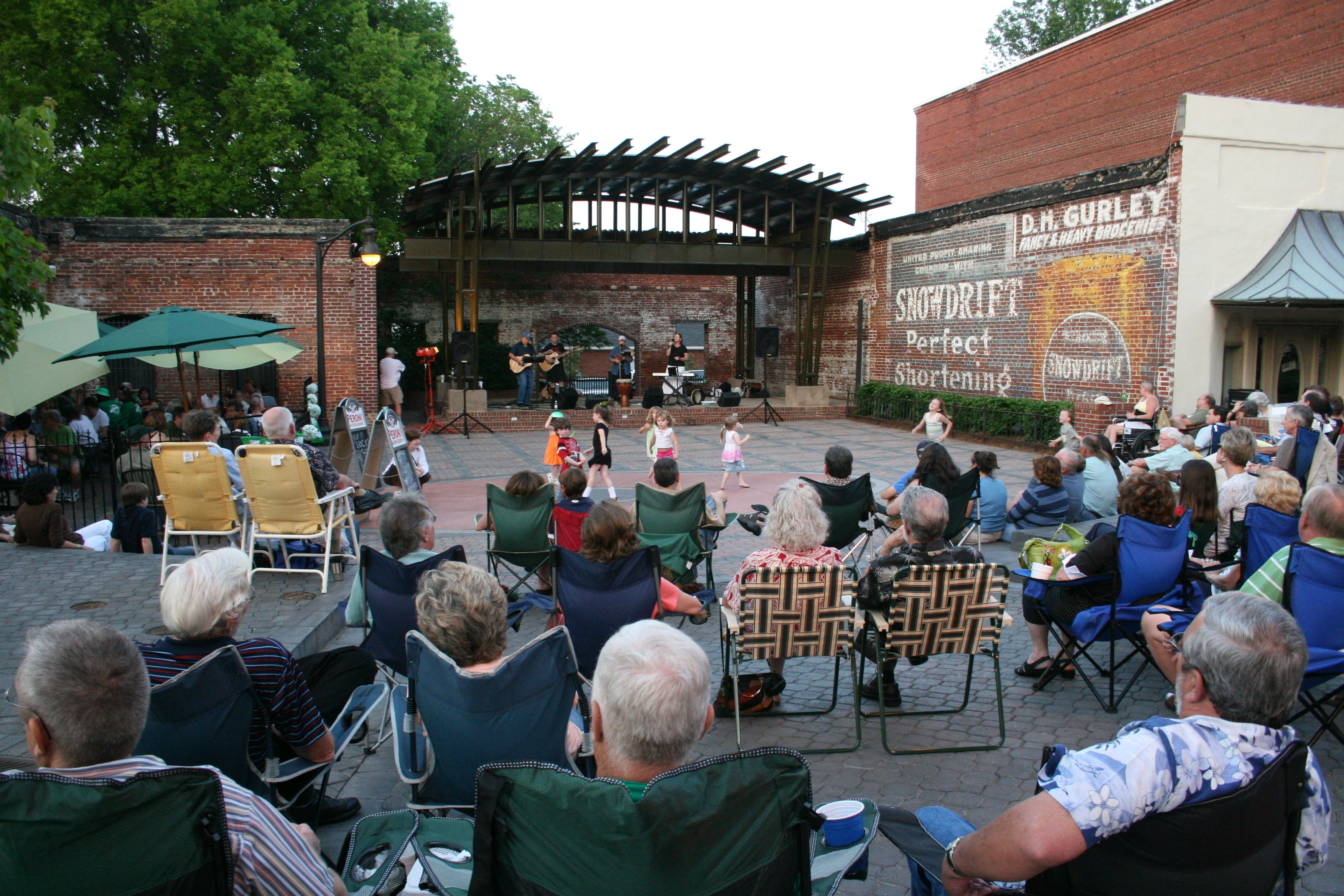 All ages enjoy a concert in O'Neal Plaza, a gathering place among historic buildings and advertisements in Douglasville, Georgia