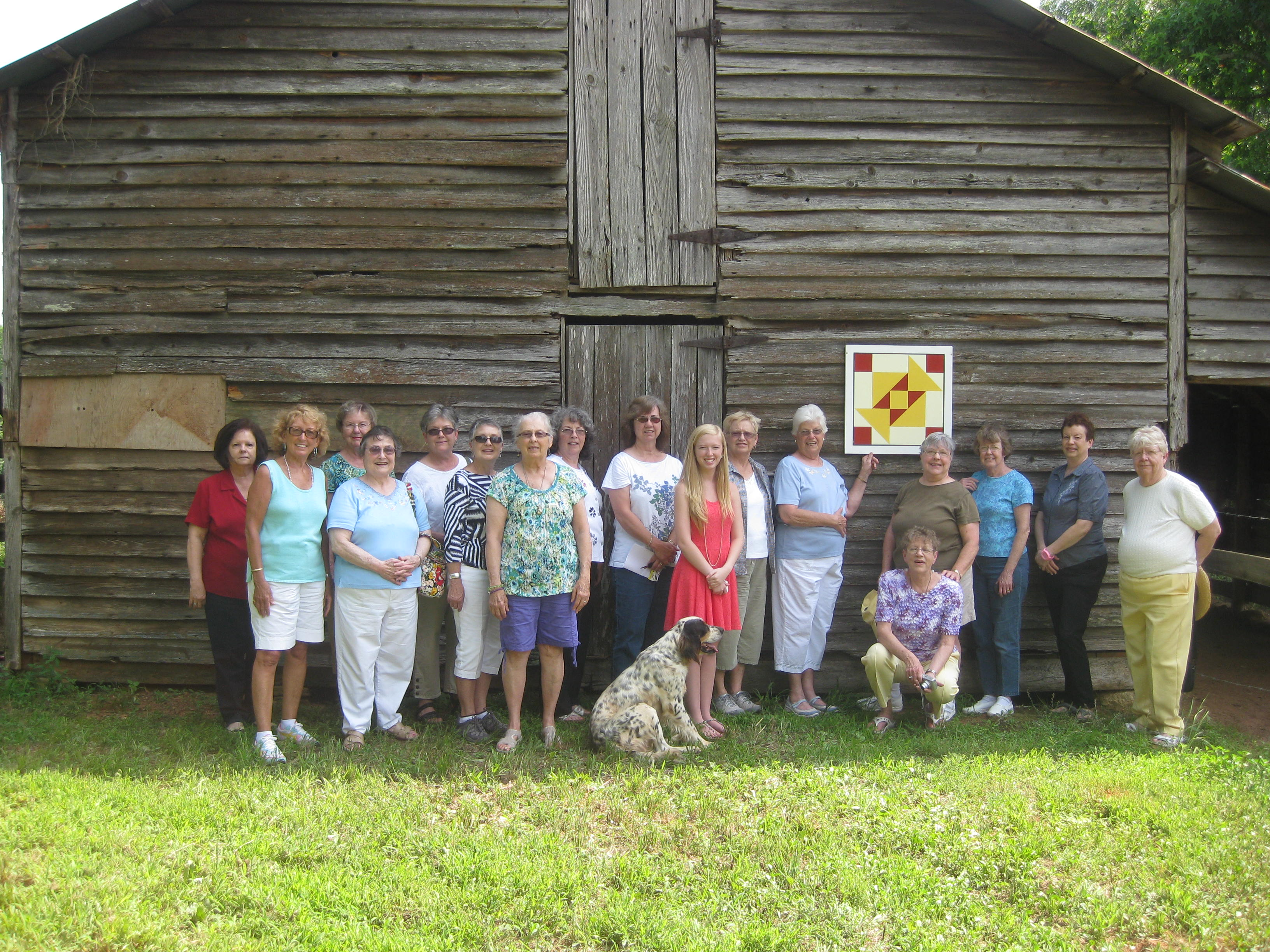 A group outside a historic barn on the Hart County Quilt Trail