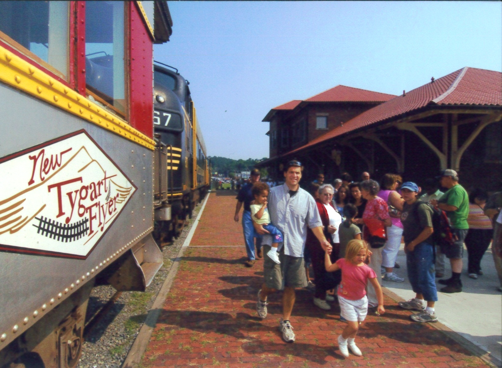 A tourist excursion train with passengers disembarking  beside the historic Elkins depot.