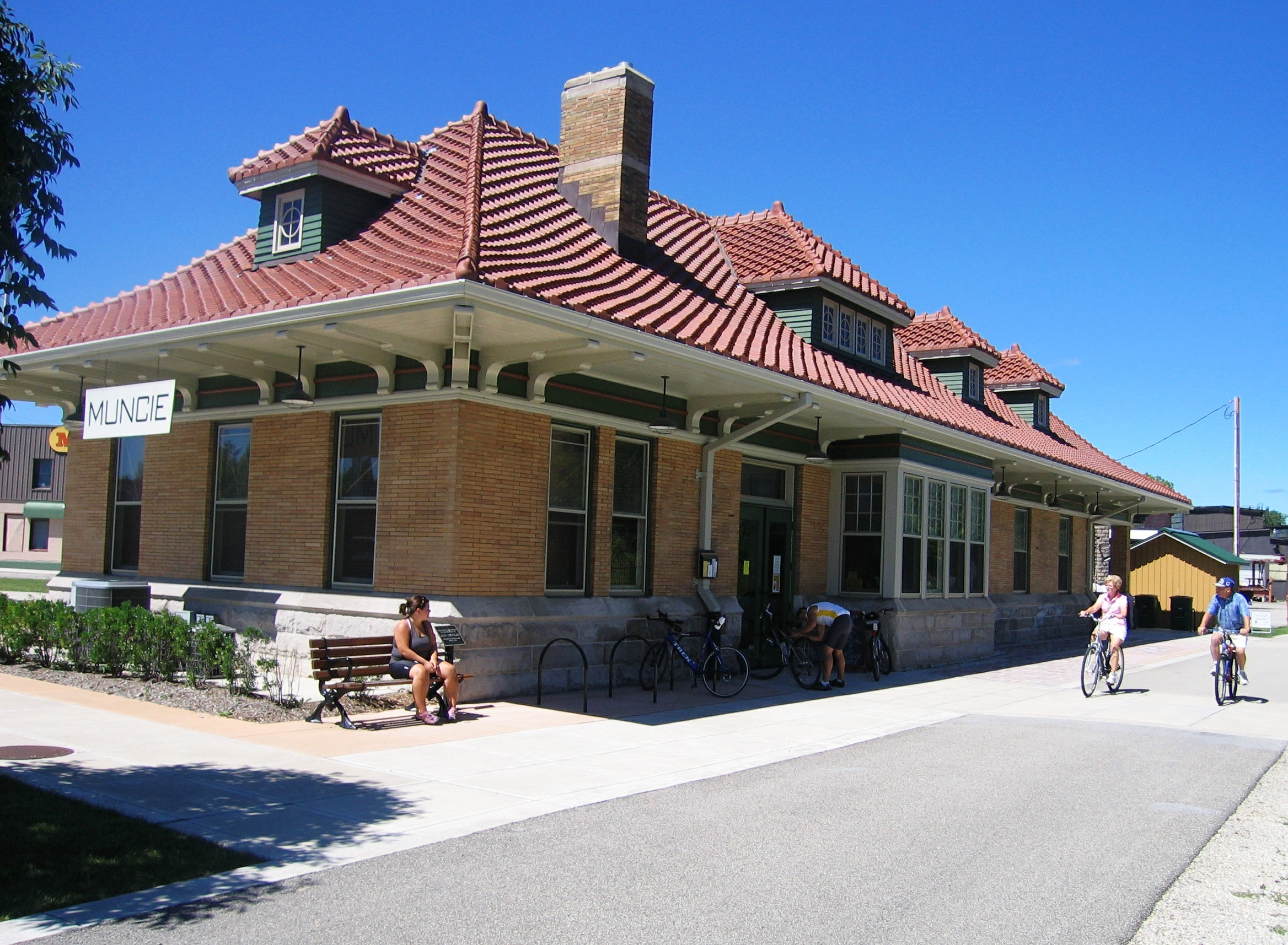 Bicyclists on the Cardinal Greenway pass by the Muncie trailhead in the restored Chesapeake and Ohio Depot (1904), listed on the National Register of Historic Places