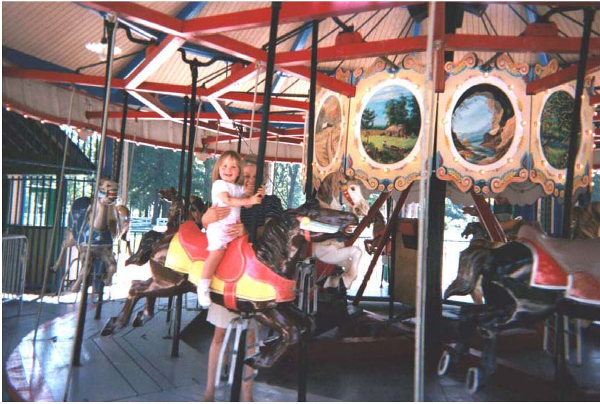 "A little girl enjoys a ride on the 1920 Allen Herschell Company ""Little Beauty"" Carousel, located in Noblesville's Forest Park."