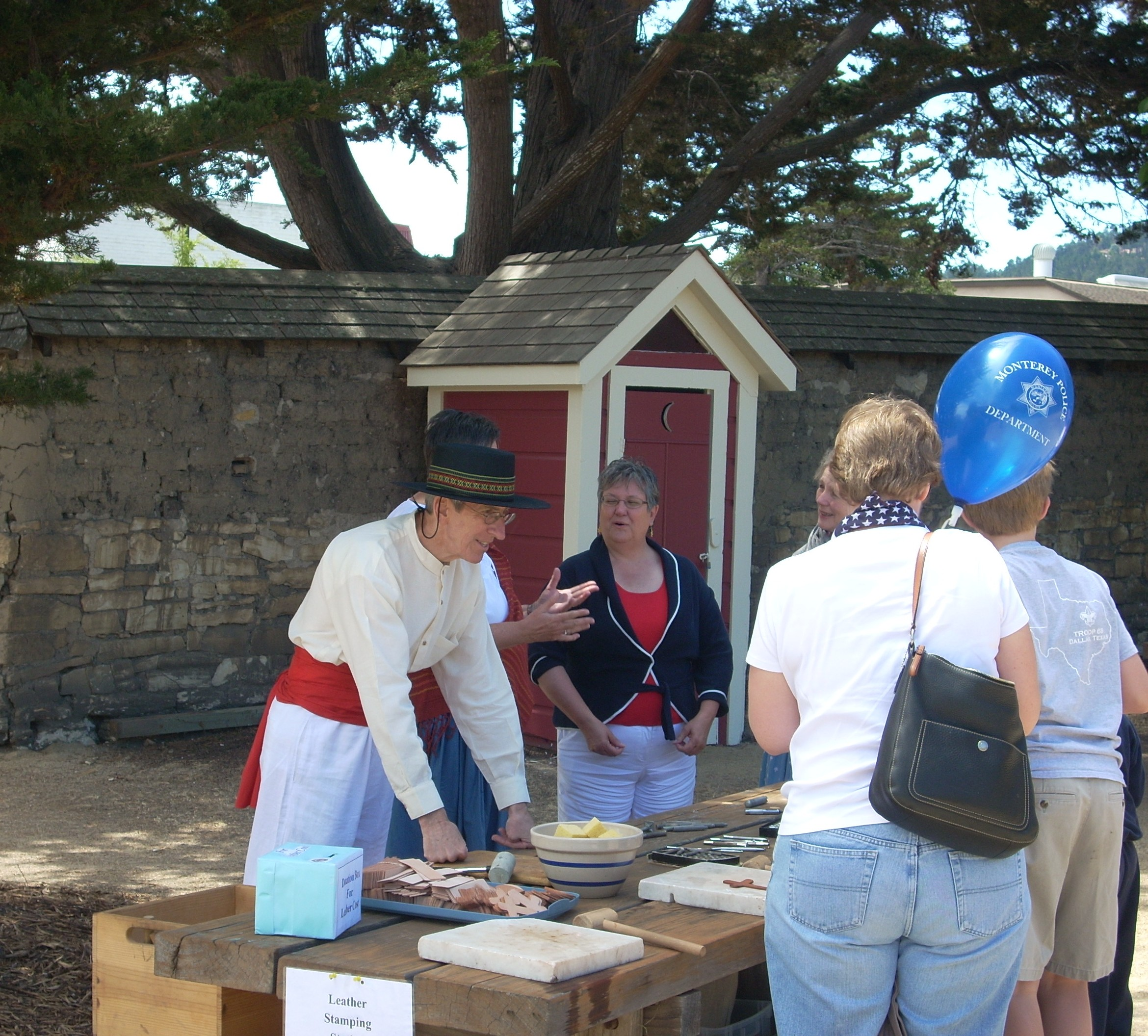 Monterey State Historic Park volunteer John Greenwald at the 2008 Cooper Molera 4th of July Living History Day.  He is working a leatherstamping station.  (Credit: John Klein. )