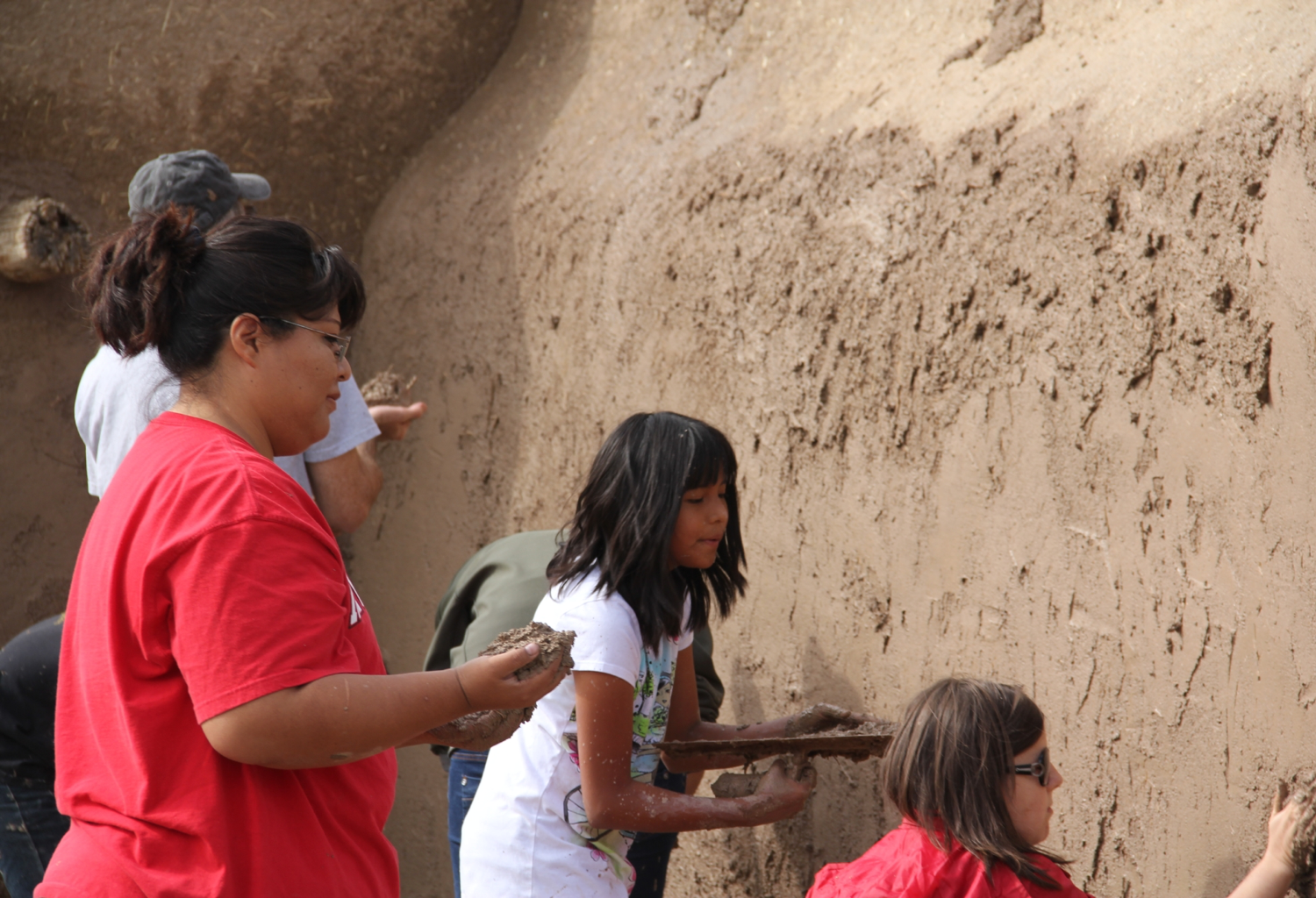 Families plastering a wall with mud